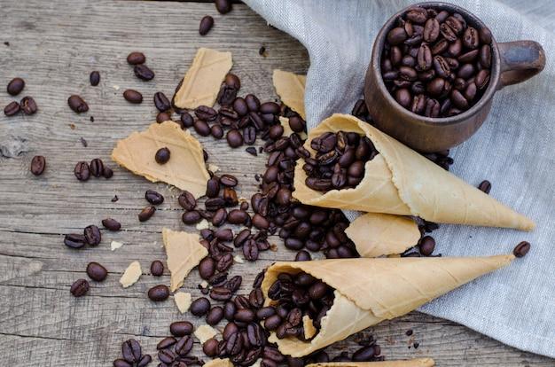 Granos de café tostados en una taza de cerámica y conos de waffle de azúcar sobre una madera