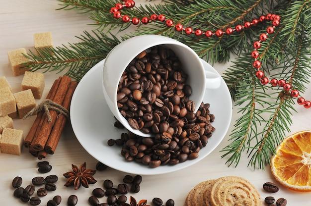 Granos de café vertidos en una taza en el fondo de navidad de azúcar, ramas de árboles, canela
