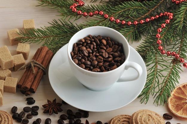 Granos de café vertidos en una taza en el fondo de navidad de azúcar