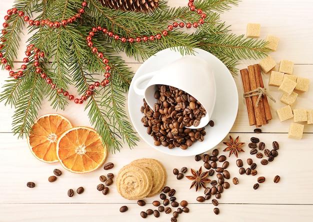 Los granos de café se vierten en una taza en el fondo de navidad de azúcar, ramas de árboles, canela y anís.
