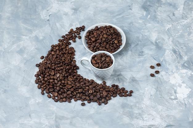 Granos de café de vista de ángulo alto en taza blanca y placa sobre fondo de yeso gris. horizontal