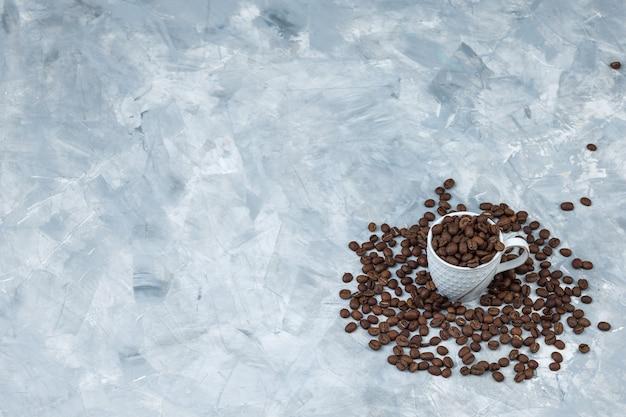Granos de café de vista de ángulo alto en taza blanca sobre fondo de yeso gris. horizontal