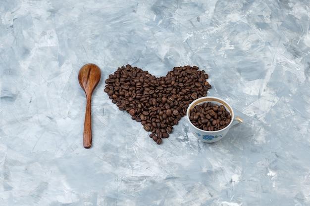 Granos de café de vista de ángulo alto en taza con cuchara de madera sobre fondo de yeso gris. horizontal