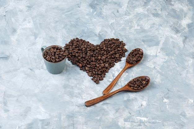 Granos de café de vista de ángulo alto en taza y cucharas de madera sobre fondo de yeso gris. horizontal