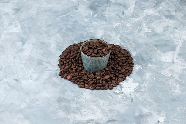Granos de café de vista de ángulo alto en taza sobre fondo de yeso gris. horizontal