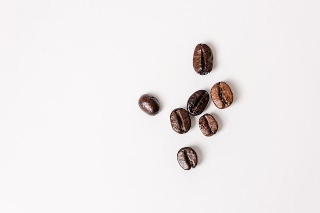 Granos de café vista superior sobre un fondo blanco.
