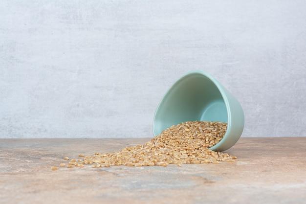 Granos de cebada del recipiente sobre la superficie de mármol