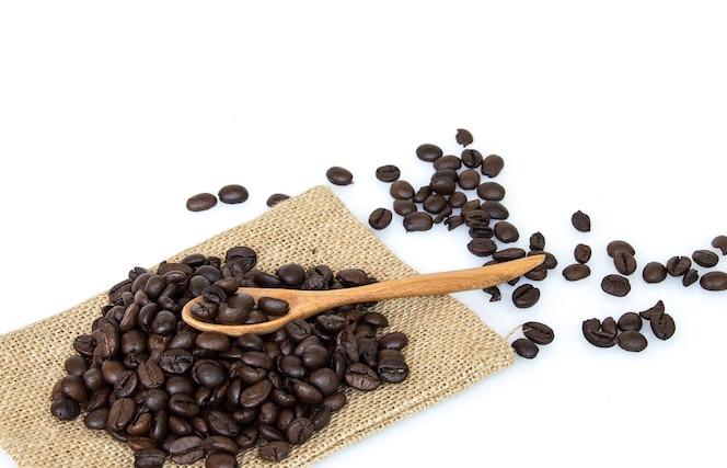 Granos de café con cuchara sobre fondo blanco