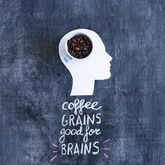 Granos de café en la taza en la cabeza del recorte blanco con texto sobre la pizarra