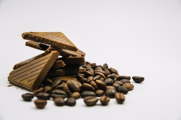 Granos de café tostados y trozos de chocolate sobre fondo blanco