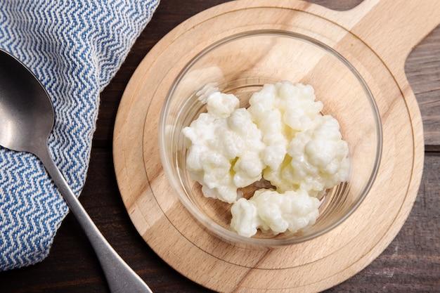 Granos de kéfir de leche en frasco en mesa de madera