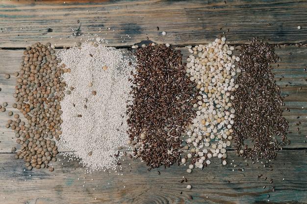 Granos libres de gluten (arroz integral, guisantes, semillas de lino, lentejas, quinua blanca) sobre fondo de madera.