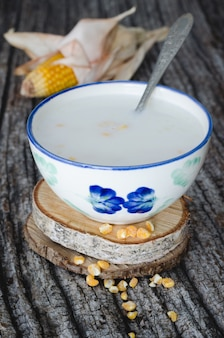 Granos de maíz cocidos con leche en la mesa de madera envejecida