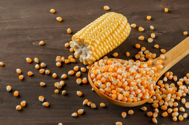 Granos de maíz en una cuchara de madera con rodaja de mazorca vista de ángulo alto sobre una mesa de madera