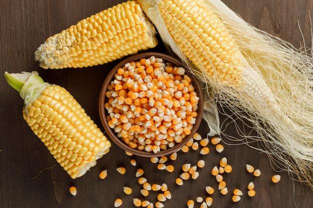 Granos de maíz en una placa de arcilla con mazorcas vista superior sobre una mesa de madera oscura