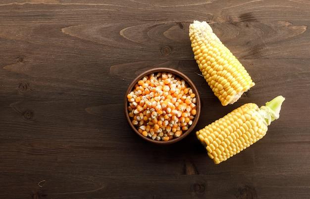 Granos de maíz en un plato de arcilla con rodajas vista superior sobre una mesa de madera