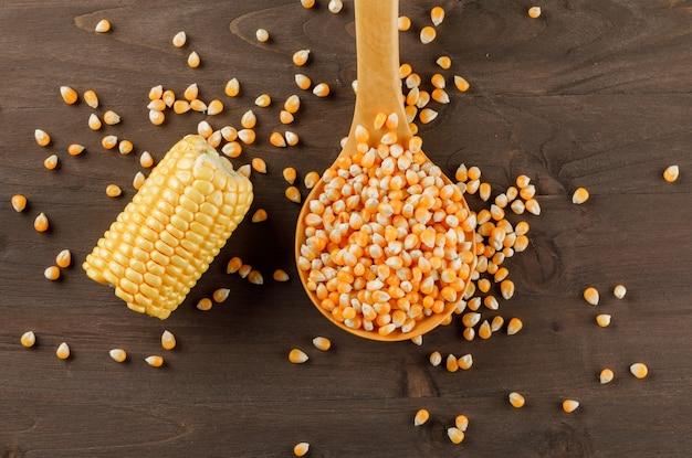 Granos de maíz con una rodaja de mazorca en una cuchara de madera sobre una mesa de madera, plana.