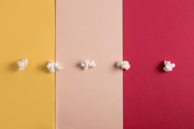 Granos de palomitas de maíz sobre un fondo multicolor. géneros cinematográficos conceptuales. romántico, comedia, musical, géneros cinematográficos