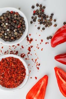 Granos de pimienta mezclados en un plato con chile en polvo y pimientos rojos de cerca en una pared blanca