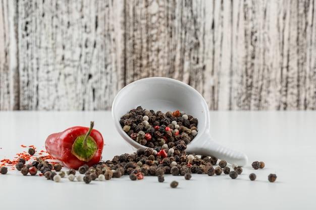 Granos de pimienta mezclados en un plato con vista lateral de pimiento rojo en la pared de grunge blanco y madera