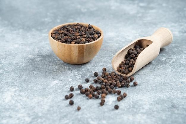 Granos de pimienta negra sobre fondo de mármol.