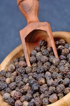 Granos de pimienta negra en un tazón de bambú
