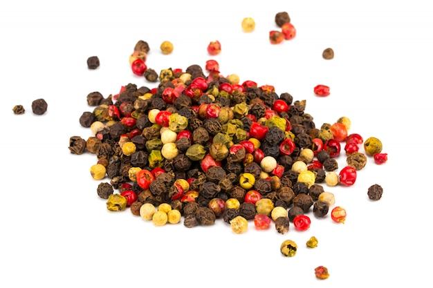 Granos de pimienta negros, rojos y blancos aislados en blanco. montón de especias. mezcla de diferentes pimientos
