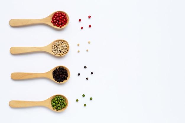 Granos de pimienta verde, rojo, blanco y negro con cuchara de madera en blanco