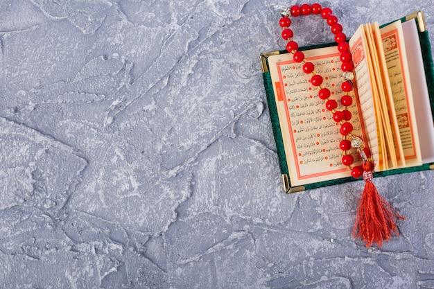 Granos de rosario rojo brillante en un sagrado kuran abierto sobre el fondo texturizado concreto