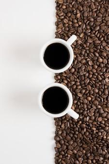 Granos tostados de café y tazas de café blanco.
