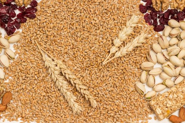 Granos de trigo y espiguillas de trigo, nueces, pasas.