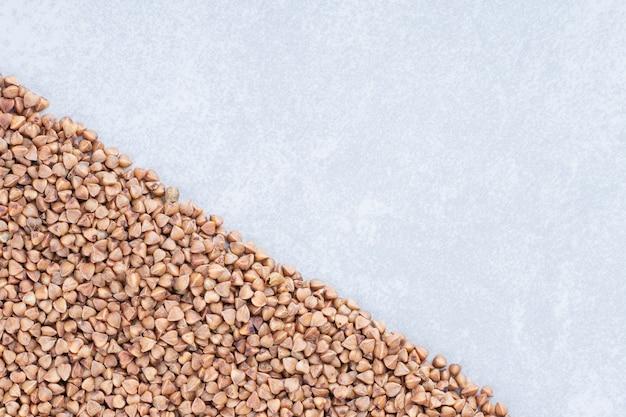Granos de trigo sarraceno apilados en forma triangular sobre la superficie de mármol