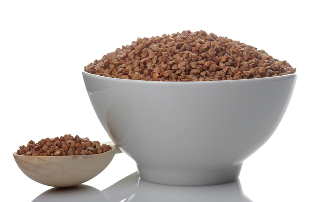 Granos de trigo sarraceno en un recipiente blanco con una cuchara sobre un fondo blanco aislado