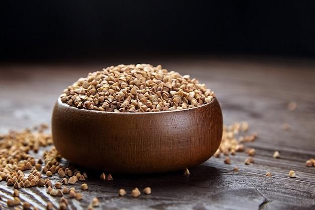 Granos de trigo sarraceno (semillas peladas) en un tazón de madera. granos integrales de trigo sarraceno en mesa marrón