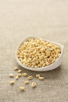 Granos de trigo en un tazón de cerámica blanco sobre fondo de tela de saco