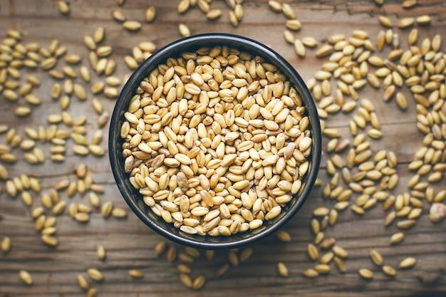 Granos de trigo en un tazón y palomitas de maíz en un tazón, semilla de trigo rústica