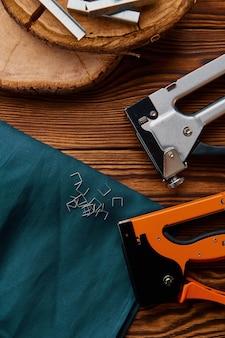 Grapadora y grapas en tocón, primer plano. instrumento profesional, equipo de carpintero, herramientas de carpintero.