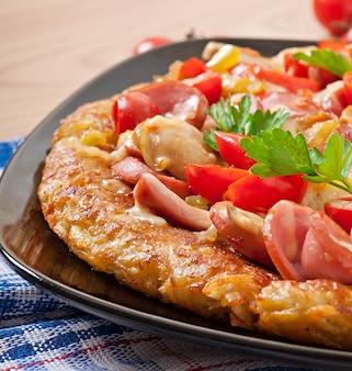Gratinado de papas - pizza con salchichas, champiñones y tomates