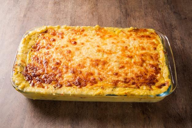 Gratinado de patatas con jamón y queso parmesano, nata y delicioso tocino curado del tirol del sur recién servido del horno sobre una mesa de madera