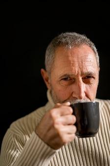 Grave anciano masculino bebiendo y mirando a cámara
