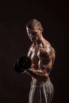 Grave atleta sin camisa tatuado levantando pesas entrenamiento sobre fondo oscuro