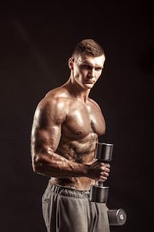 Grave atleta sin camisa tatuado levantando pesas de metal entrenamiento sobre fondo oscuro