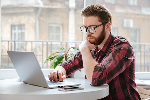 Grave barbudo joven usando la computadora portátil.