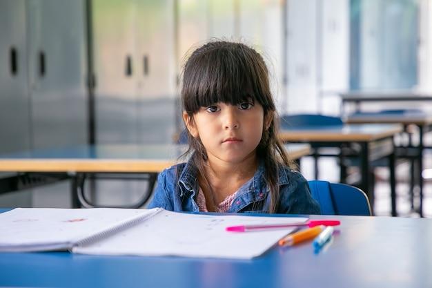 Grave chica latina sentada en el escritorio de la escuela y mirando al frente