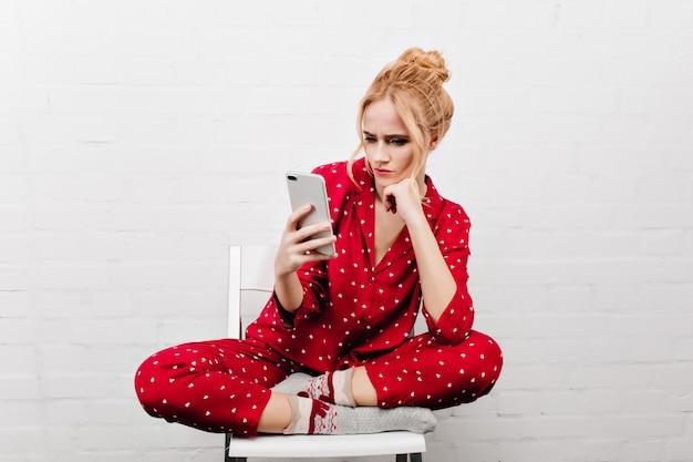 Grave chica en ropa de dormir roja sentada con las piernas cruzadas sobre la pared blanca. retrato de interior de mujer joven molesta posando en silla con teléfono.