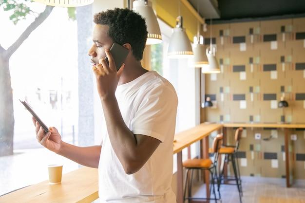 Grave chico afroamericano hablando por celular y mirando la pantalla de la tableta