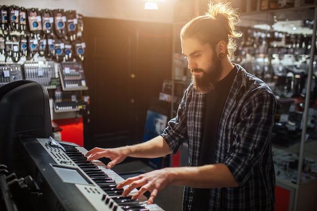 Grave y concentrado hipster joven sentarse y tocar en el teclado. está solo en la habitación. hace sol adentro.