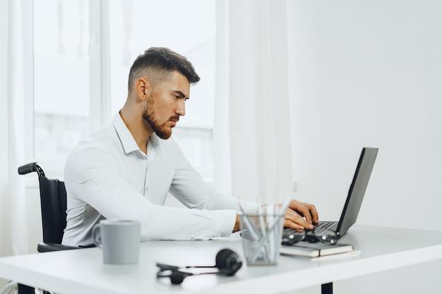 Grave discapacitado concentrado en silla de ruedas usando su computadora portátil para el trabajo