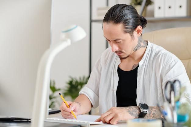 Grave diseñador gráfico creativo concentrado dibujo boceto de logotipo con lápiz sobre hoja de papel