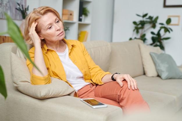 Grave empresaria rubia en ropa casual pensando en ideas para el plan de trabajo mientras está sentado en el sofá en la sala de estar durante la cuarentena